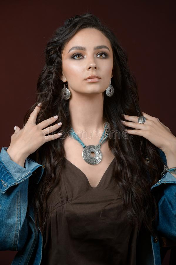 Close-up portrait beautiful young woman wearing luxury jewelry. Focus on earring and necklace royalty free stock photos