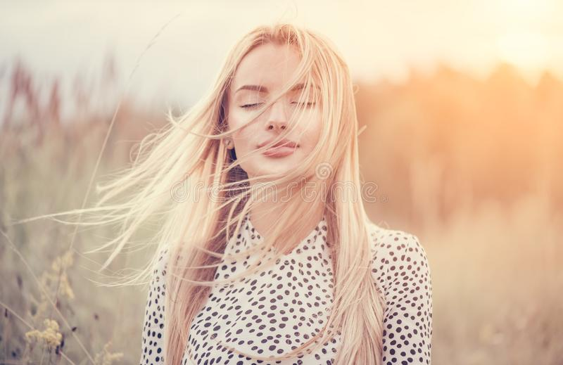 Close Up Portrait of beauty girl with fluttering white hair enjoying nature outdoors, on a field. Flying blonde hair on the wind. Breeze playing with girl`s royalty free stock photo