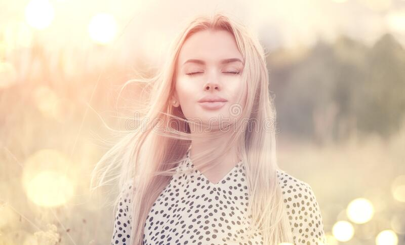 Close Up Portrait of beauty girl with fluttering white hair enjoying nature outdoors, on a field. Flying blonde hair on the wind stock photography