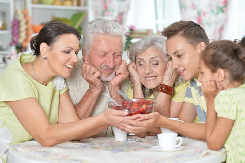 Close up portrait of big happy family eating fresh strawberries. Big happy family eating fresh strawberries at kitchen royalty free stock photography