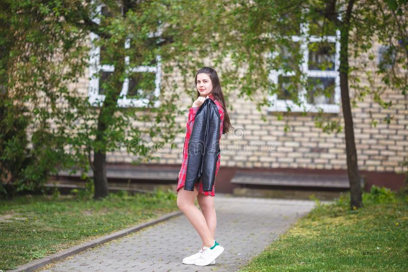 Close up portrait of big plus size beautiful stylish kid girl with leather jacket  and red plaid shirt near brick building in royalty free stock photo