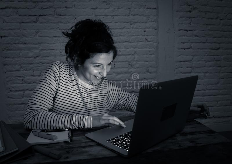 Portrait of a happy young woman working on laptop late at night. In education and working concept stock image
