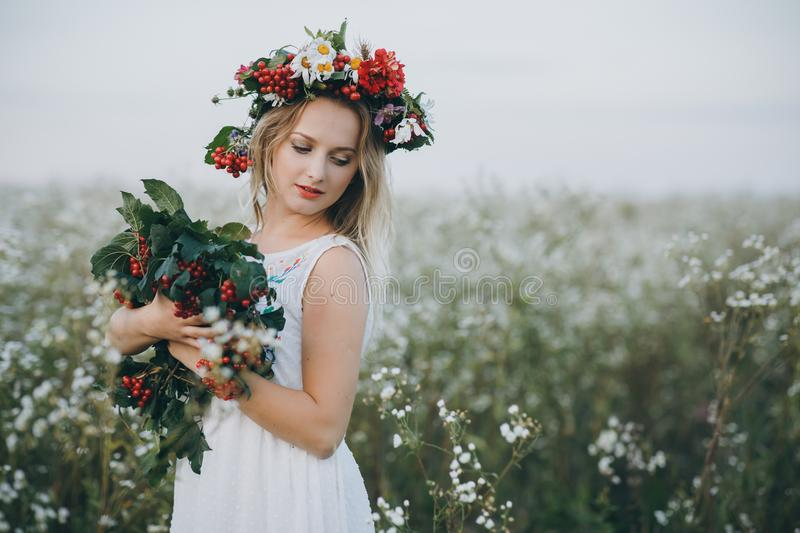 Close up Portrait of a blonde girl with blue eyes with a wreath of flowers on her head royalty free stock photos