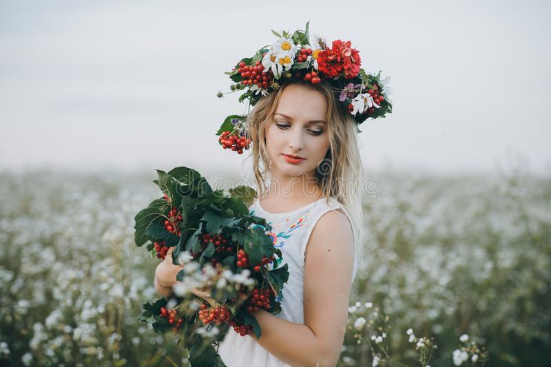Close up Portrait of a blonde girl with blue eyes with a wreath of flowers on her head stock photography