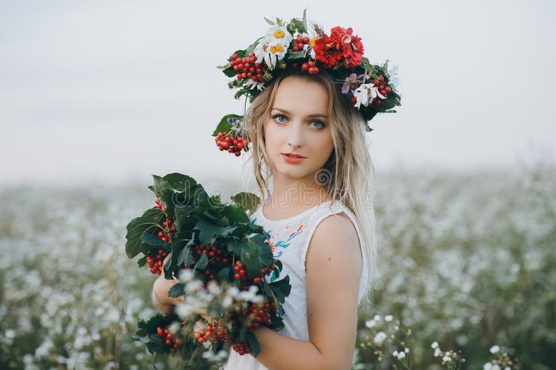 Close up Portrait of a blonde girl with blue eyes with a wreath of flowers on her head stock image
