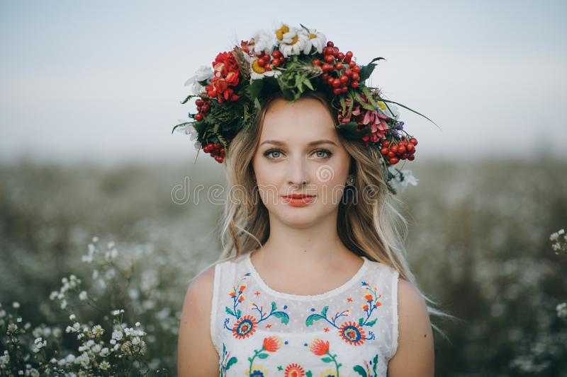 Close-up Portrait of a blonde girl with blue eyes with a wreath of flowers on her head stock photos