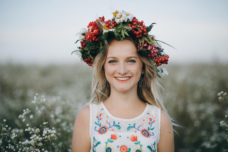 Close-up Portrait of a blonde girl with blue eyes with a wreath of flowers on her head stock images