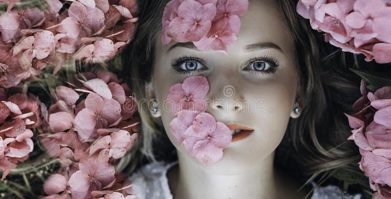 Close-up portrait of a girl lying on the ground with flowers of hydrangea on her face royalty free stock image