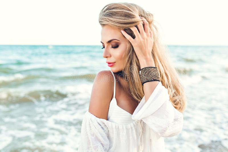 Close-up portrait of blonde girl with long hair dreaming on sea background. She wears white clothes and ornamentation on. Hand. She looks down stock images