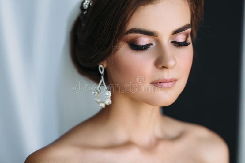 Close-up portrait of the bride with diamond earrings, wedding make-up and hairdo poses in a dark studio. Beautiful young. Brunette girl on black and white royalty free stock image