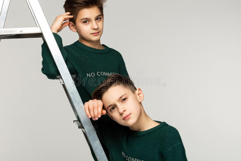 Close up portrait of brothers teenagers in green sweaters stock photo