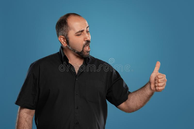 Close-up portrait of a brunet middle-aged man with beard, dressed in a black t-shirt and posing against a blue stock photography