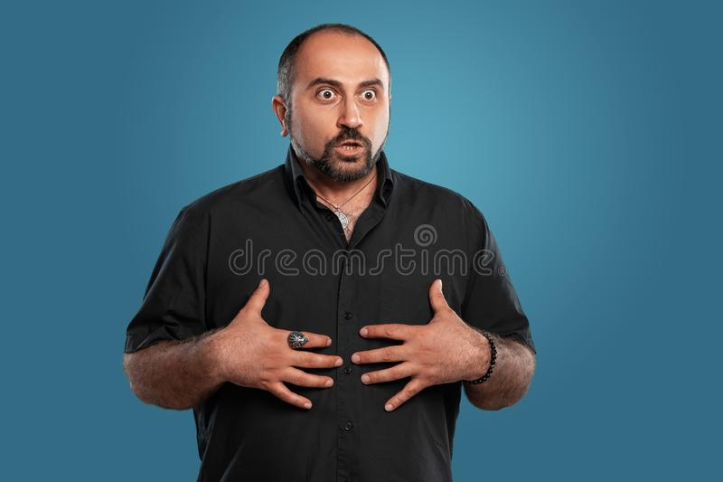 Close-up portrait of a brunet middle-aged man with beard, dressed in a black t-shirt and posing against a blue. Close-up portrait of a brunet handsome middle royalty free stock photo