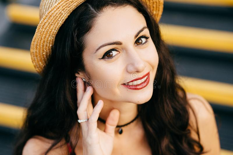Close up portrait of brunette female looking with her dark eyes, red painted lips into camera wearing straw hat keeping her hand o royalty free stock images