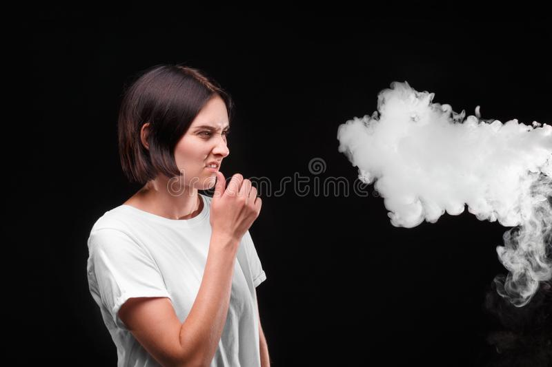 A woman wrinkles because of the cigarette or an electronic cigarette smoke on a black background. Healthcare concept. A close-up portrait of a brunette girl in royalty free stock photos
