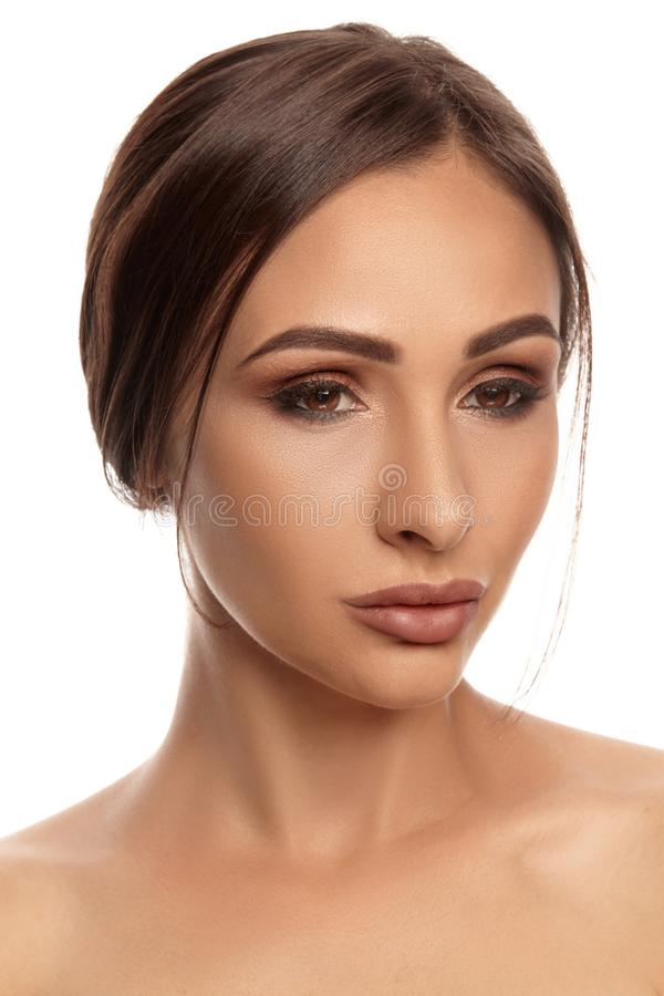 Close up portrait of a brunette nude model girl with professional evening make-up and plump lips, posing isolated on royalty free stock images