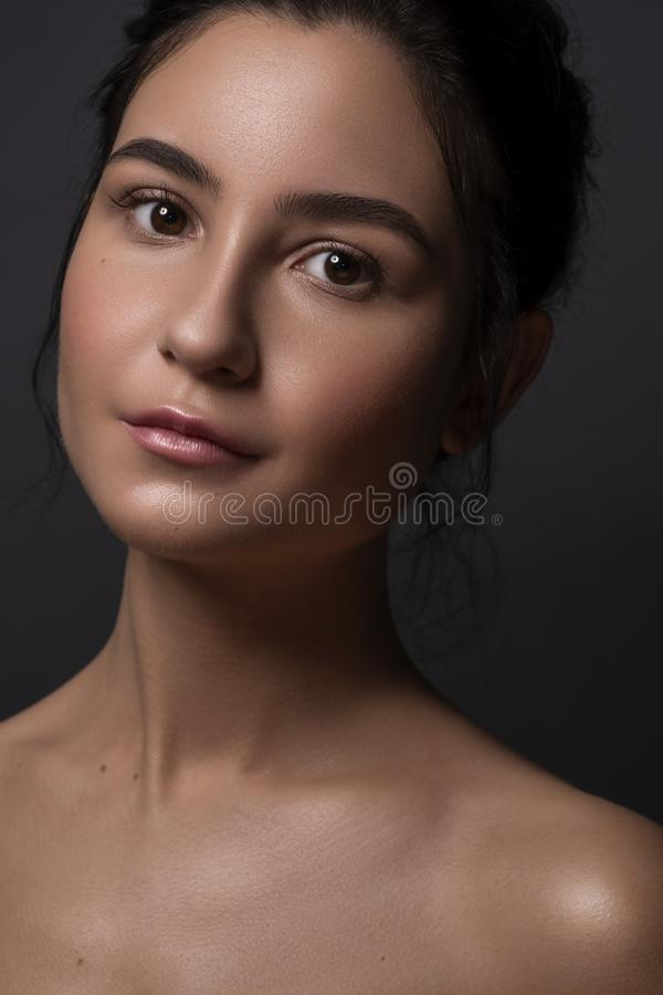 Close up portrait of Brunette woman with flawless clean skin. Natural neutral make up. Studio concept.  stock photos