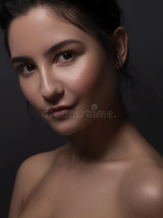 Close up portrait of Brunette woman with flawless clean skin. Natural neutral make up. Studio concept.  royalty free stock image