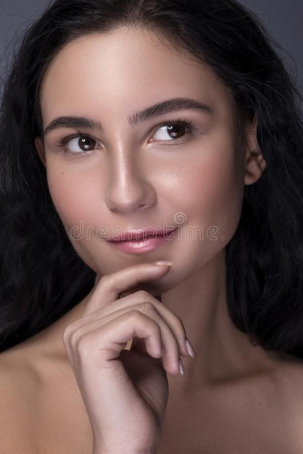 Close up portrait of Brunette woman with flawless clean skin. Natural neutral make up. Studio concept.  stock images