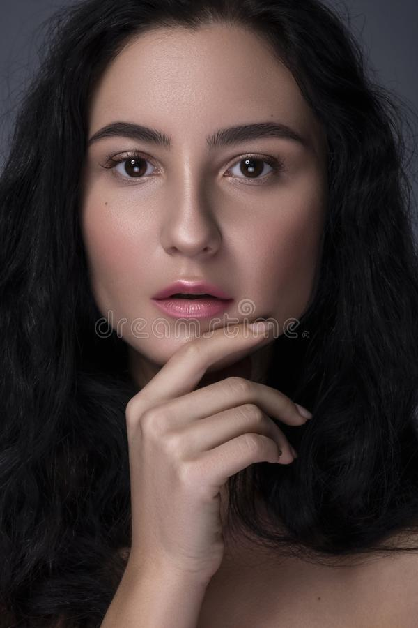 Close up portrait of Brunette woman with flawless clean skin. Natural neutral make up. Studio concept.  stock photo