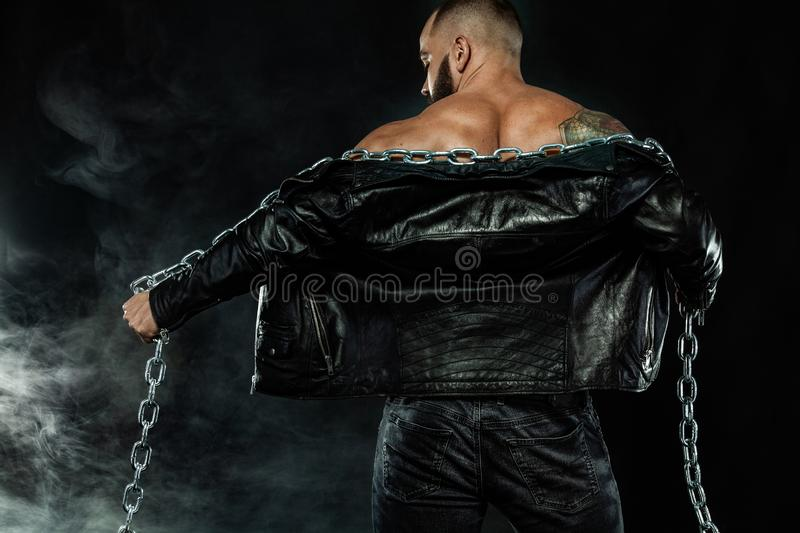 Men fashion. Close-up portrait of a brutal bearded man topless in a leather jacket with chains. Athlete bodybuilder on stock photography