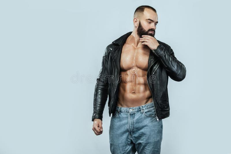 Close-up portrait of a brutal bearded man topless in a leather jacket stock photo