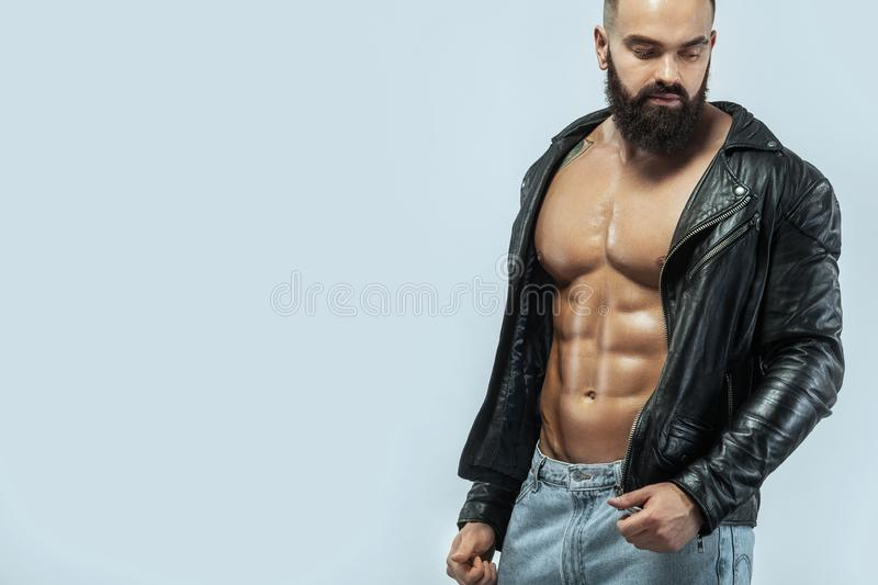 Close-up portrait of a brutal bearded man topless in a leather jacket stock image