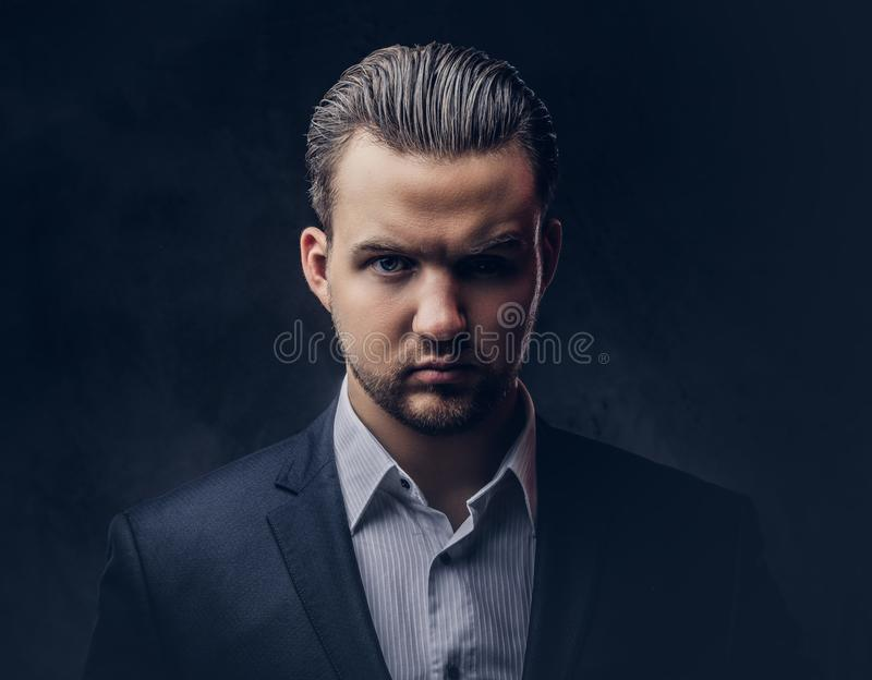 Close-up portrait of a brutal businessman with serious face in an elegant formal suit. Isolated on a dark background. royalty free stock images