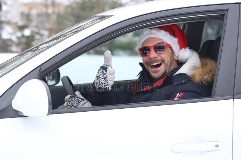 Close up portrait of car driver with santa hat and thumb up enjoying the snow and sunny dan. stock image