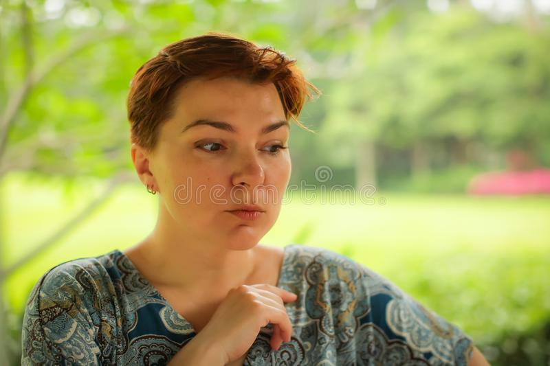 Close up portrait of carefree adult caucasian redhead woman in dress posing with different emotions in green summer park royalty free stock images