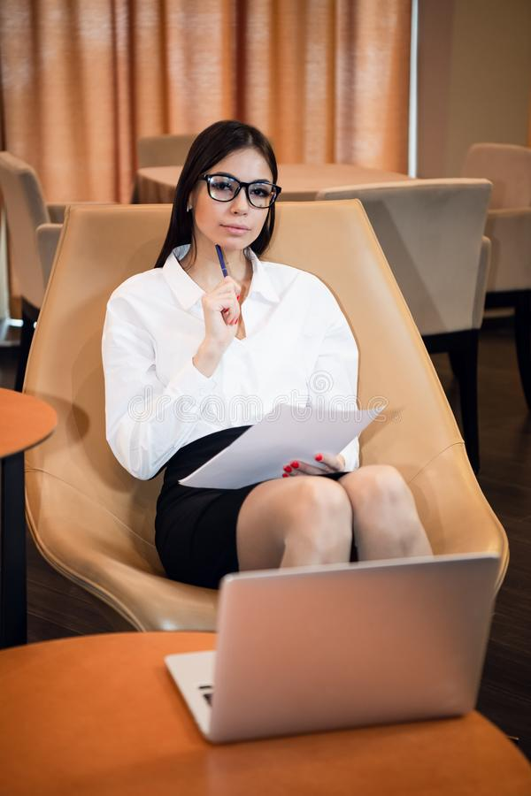 Close-up portrait of casual woman using her laptop while sitting on couch and working. stock photos