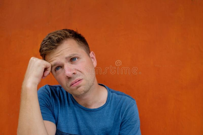 Close up portrait of caucasian disappointed stressed young man on red background. He is about to cry. stock images