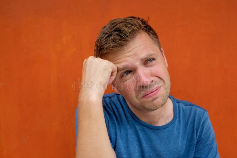 Close up portrait of caucasian disappointed stressed young man on red background. He is about to cry. stock photo
