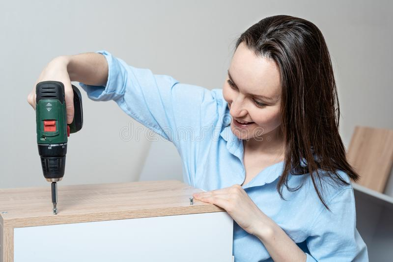 Close-up portrait of Caucasian woman with a screwdriver in hand, collects furniture stock photo