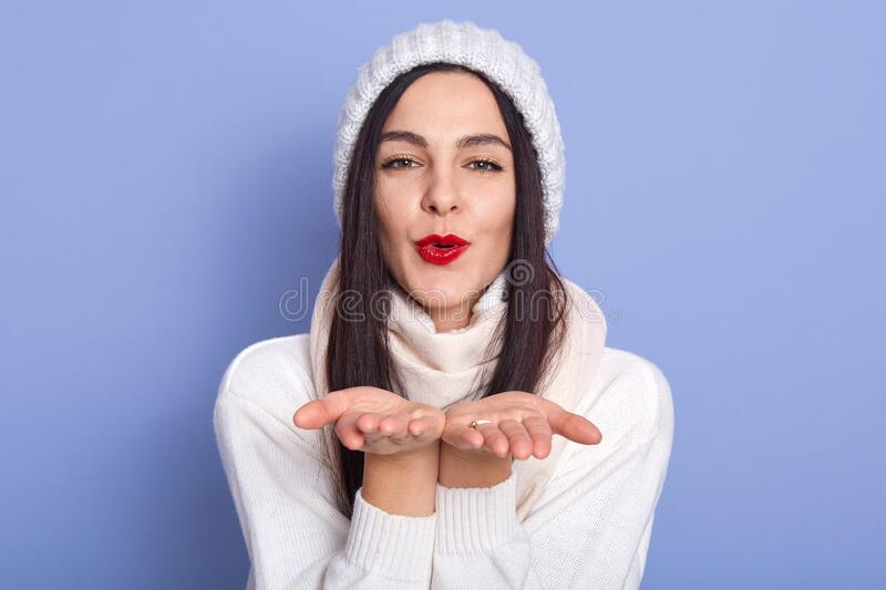 Close up portrait of charismatic lovely sweet brunette putting hands together, sending kiss, having peaceful facial expression, royalty free stock photo