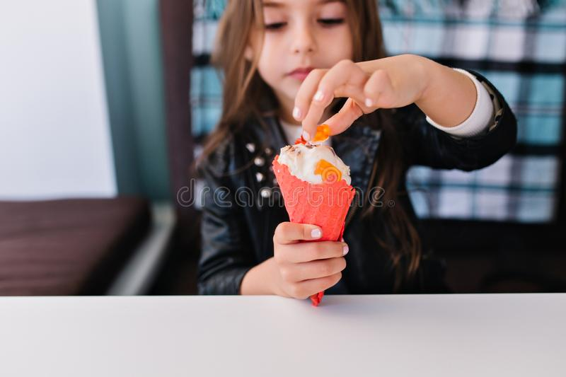 Close-up portrait of charming brunette little girl with white manicure touching her tasty cold dessert. Cute child with royalty free stock photos