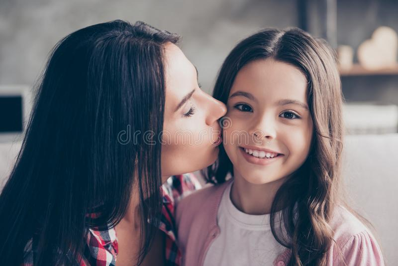 Close up portrait of charming cheerful smiling lovely mother kissing her adopted young cute beautiful girl stock photography