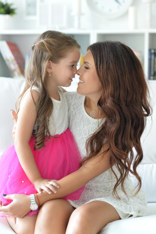 Close-up portrait of a charming little girl hugging with mom royalty free stock photos