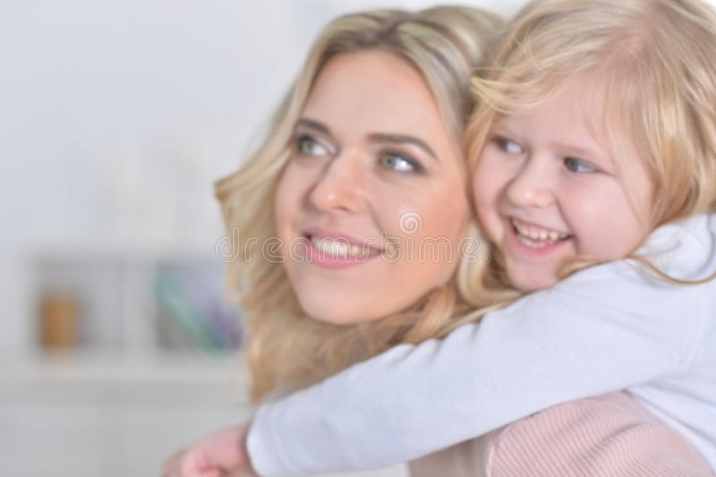 Close-up portrait of a charming little girl with mom at home royalty free stock photo
