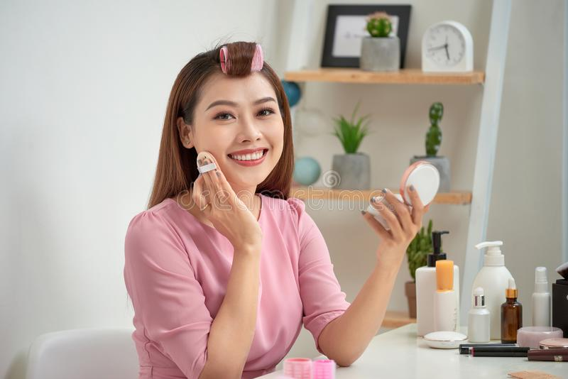 Close up portrait of charming pretty cute good-looking stylish trendy fashionable sexy applying powder with sponge on cheeks stock images