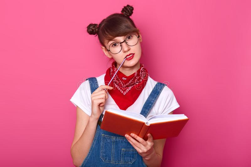 Close up portrait of charming thoughtful student in glasses thinks about something important, holds planner in hands, prepares for. Exams, keeps pensil at her royalty free stock photo