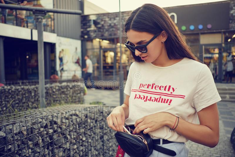 Portrait of a girl in dark sunglasses posing near a city mall. Dressed in white t-shirt, blue trousers, black waist bag. Close-up portrait of a charming young royalty free stock photo
