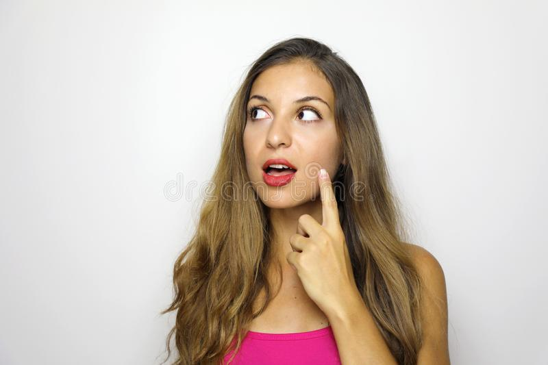Close-up portrait of charming young woman in fuchsia pink dress pointing with finger looking to the side isolated on gray. Background royalty free stock photos