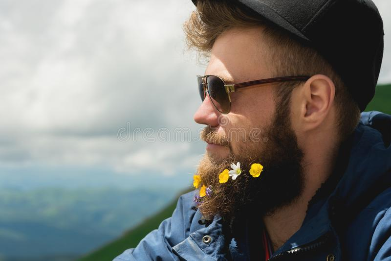 Close-up portrait of a cheerful bearded man in sunglasses and a gray cap with wildflowers in a beard. Soft brutality and stock images