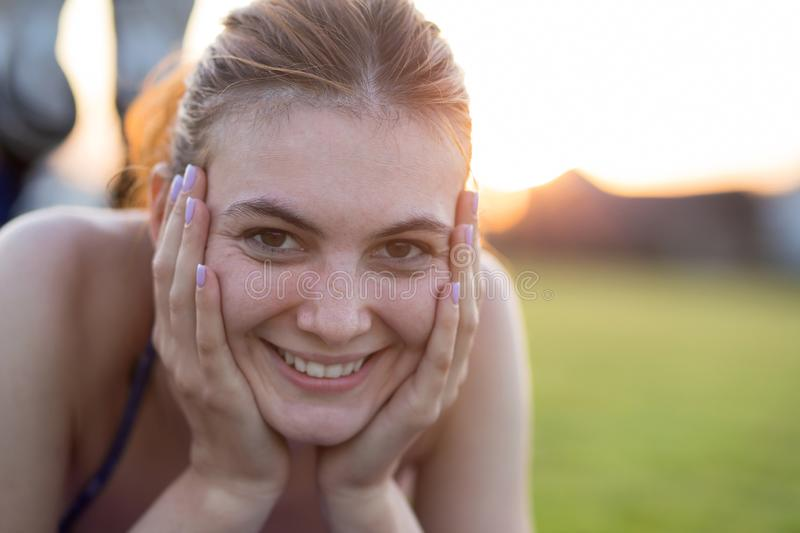 Close up portrait of cheerful smiling young girl with freckles on her face outdoors in sunny summer day. Human expressions and stock photos