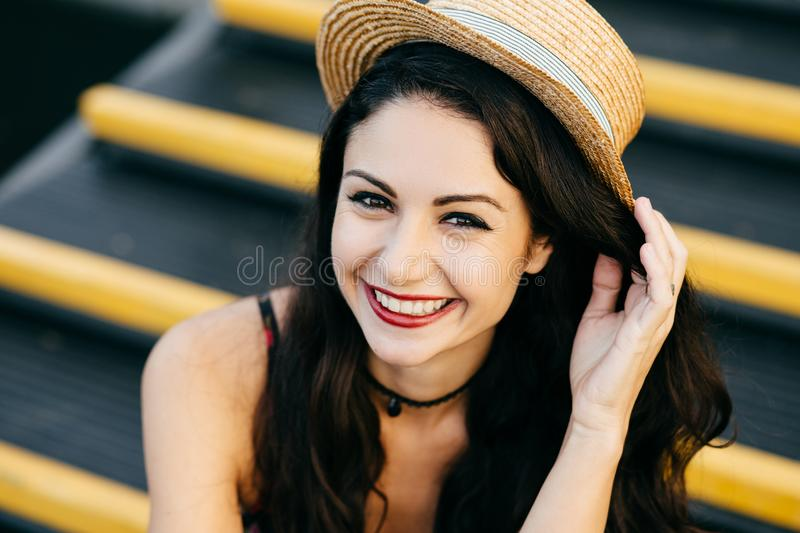 Close up portrait of cheerful woman with dark hair, eyes full of happiness and thin lips wearing straw hat, keeping hand on it, fe stock images