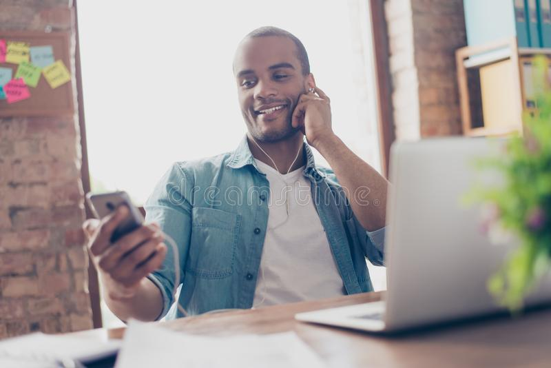 Close up portrait of cheerful young afro guy enjoying listening to nice song at his work place, on his smart phone, wearing casual royalty free stock photos