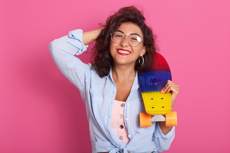 Close up portrait of cheerful young woman in casual clothes standing, looking directly at camera, holding multicoloured skateboard. Over rosy background in royalty free stock photography