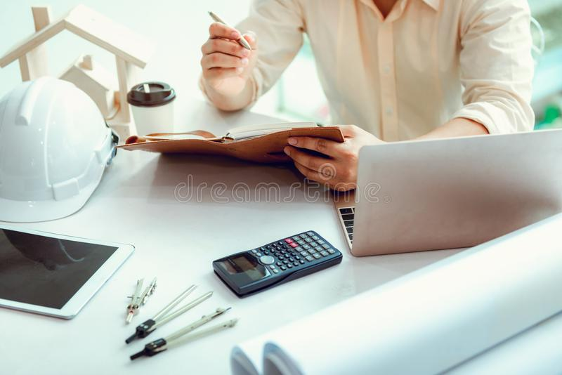 Close up portrait of civil engineer taking note construction planning report, Engineering and construction concept stock image