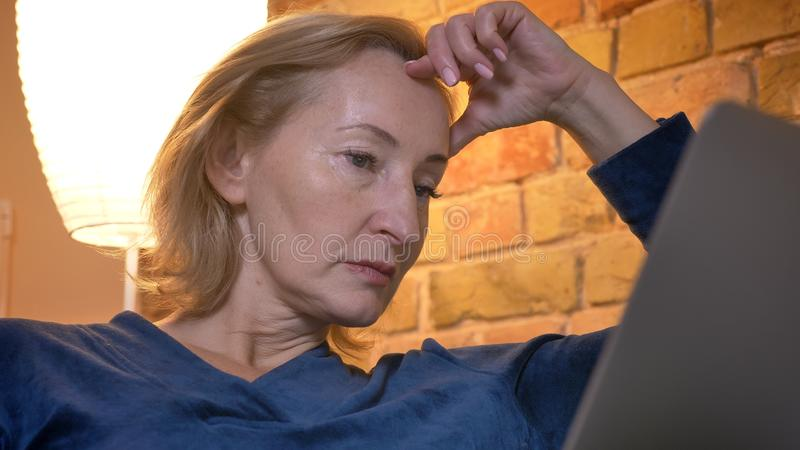 Close-up portrait of concentrated old caucasian lady working with laptop and leaning on hand in cozy home atmosphere. stock photography